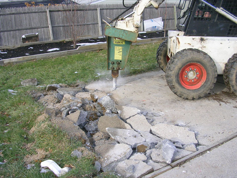 BOBCAT JACKHAMMER WORKING BREAKING CEMENT · CLOSEUP BROKEN PATIO CONCRETE  WITH WIRE